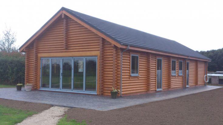 A standalone log cabin with paving